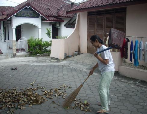 Menyapu sampah daun di halaman.